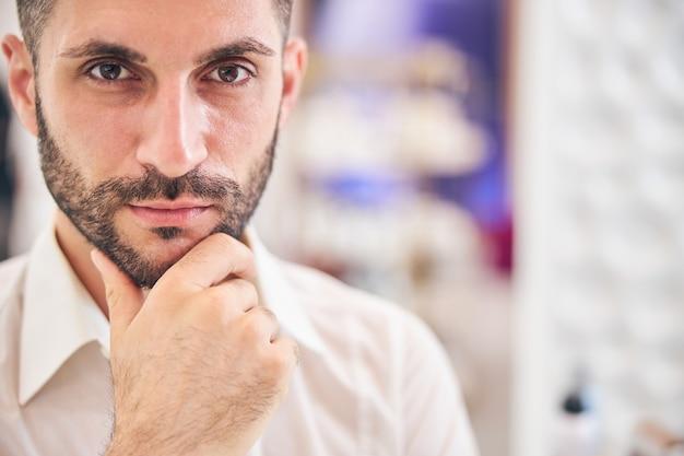 Przystojny brodaty mężczyzna dotyka brody będąc głęboko zamyślonym