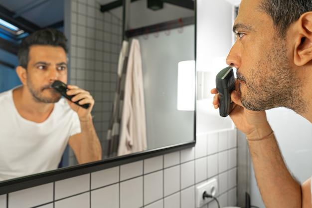 Przystojny brodaty mężczyzna goli twarz trymerem