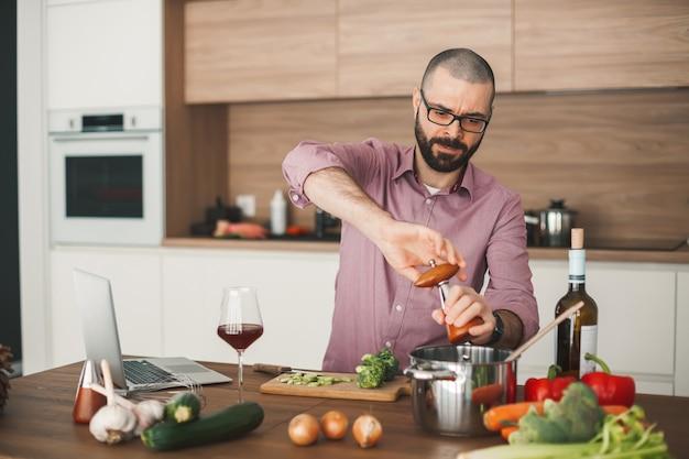 Przystojny brodaty mężczyzna gotowanie gulasz warzywny za pomocą laptopa. kroi brokuły, cukinię, czerwoną paprykę, cebulę i inne warzywa.