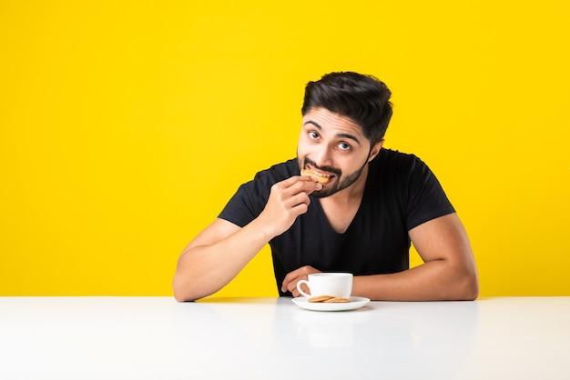 Przystojny brodaty mężczyzna indyjski jedzenie zdrowe herbatniki pełnoziarniste zanurzone w kawie herbaty lub czaj w filiżance, siedząc przy stole na żółtym tle
