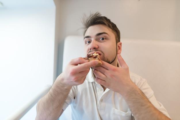 Przystojny brodaty mężczyzna je apetyczną pizzę i patrzy w kamerę. pizza na lunch.