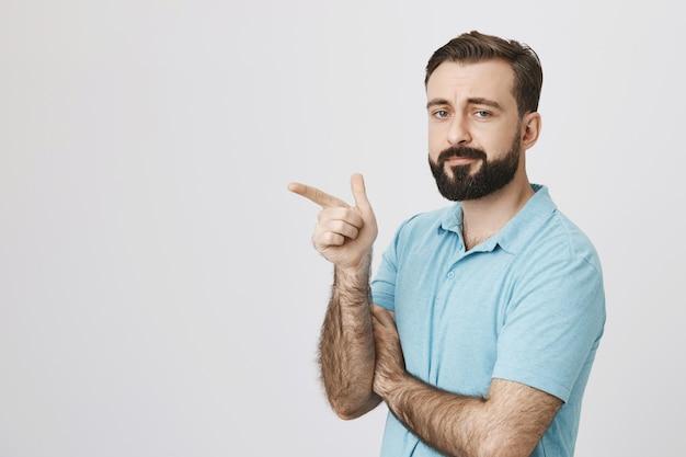 Przystojny brodaty mężczyzna klient dokonuje wyboru, wskazując w lewo
