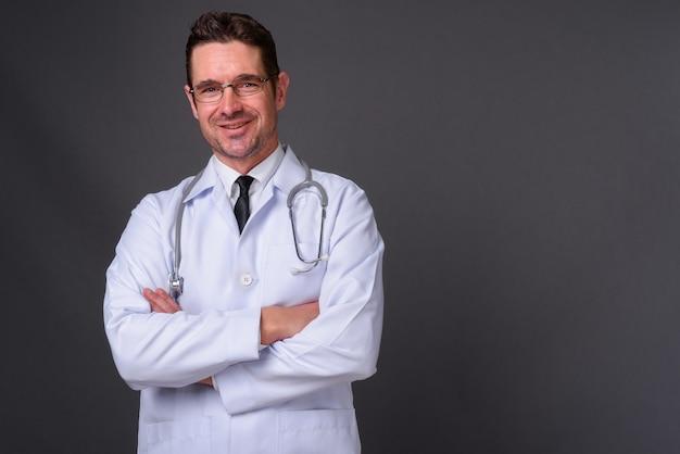 Przystojny brodaty mężczyzna lekarz z okularami na szarej ścianie