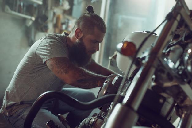Przystojny brodaty mężczyzna naprawia jego motocykl w garażu. mężczyzna w dżinsach i koszulce