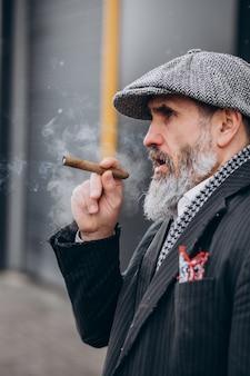 Przystojny brodaty mężczyzna palący papierosa