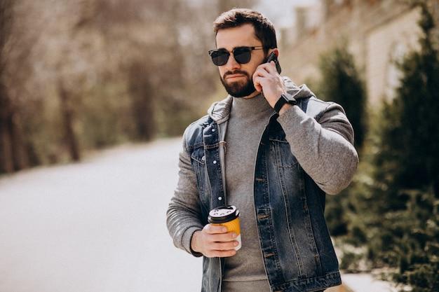 Przystojny brodaty mężczyzna pije kawę na zewnątrz ulicy