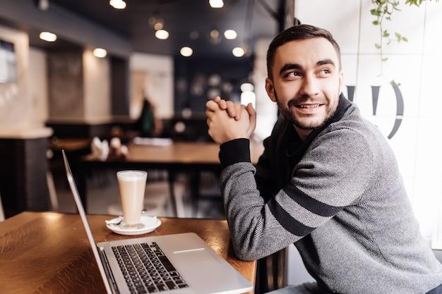 Przystojny brodaty mężczyzna pije kawę podczas pracy w kawiarni