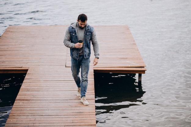 Przystojny brodaty mężczyzna pije kawę rzeką w parku