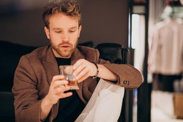 Przystojny brodaty mężczyzna pije whisky