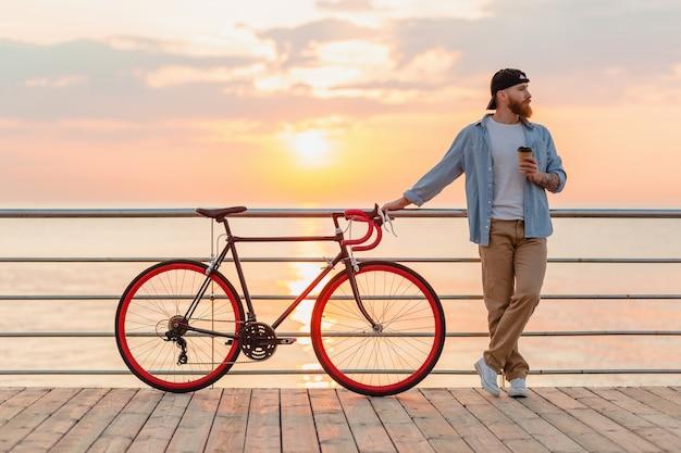 Przystojny brodaty mężczyzna podróżujący rowerem w poranny wschód słońca nad morzem pije kawę, podróżnik zdrowego, aktywnego stylu życia