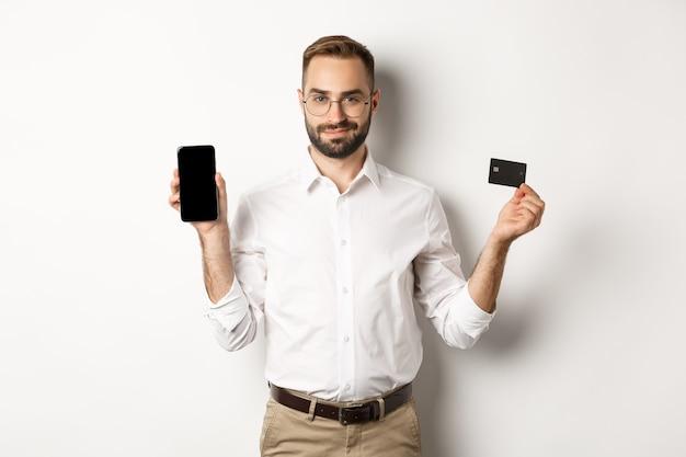 Przystojny brodaty mężczyzna pokazuje telefon komórkowy i kartę kredytową, zakupy online, stojąc na białym tle.