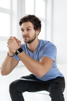 Przystojny brodaty mężczyzna robi przysiady z pętlą oporową podczas treningu na siłowni