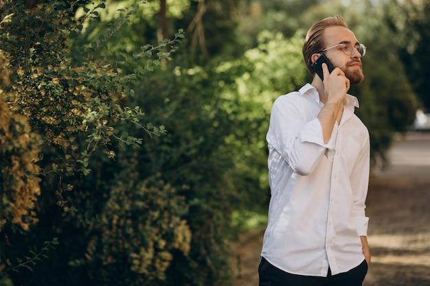 Przystojny brodaty mężczyzna rozmawia przez telefon
