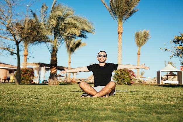 Przystojny brodaty mężczyzna siedzi na zielonej trawie i wznosi dłonie do słońca w okularach przeciwsłonecznych.