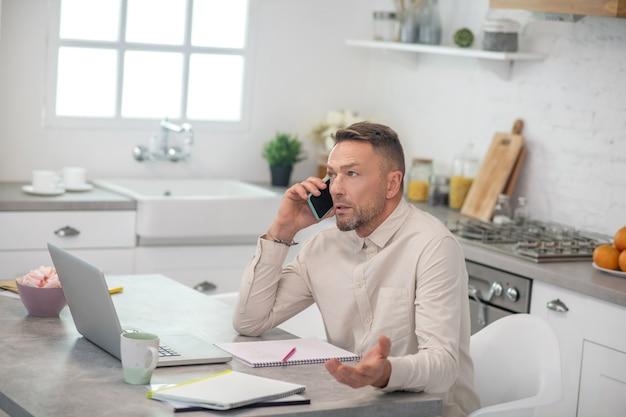 Przystojny brodaty mężczyzna siedzi w kuchni i rozmawia przez telefon