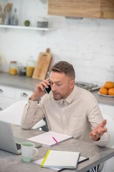 Przystojny brodaty mężczyzna siedzi w kuchni i rozmawia
