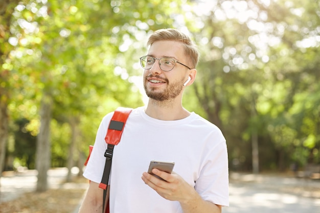 Przystojny brodaty mężczyzna spaceruje po parku z telefonem w dłoni, ubrany w zwykłe ubranie i czerwony plecak, szeroko się uśmiecha i odwraca wzrok