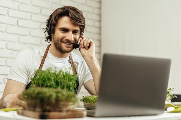 Przystojny, brodaty mężczyzna sprzedaje kiełki i sadzonki roślin online za pomocą laptopa