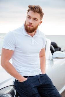 Przystojny brodaty mężczyzna stojący w pobliżu nowoczesnego samochodu na plaży