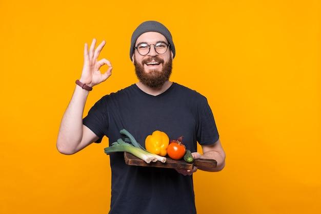 Przystojny brodaty mężczyzna trzyma deskę do krojenia z niektórymi warzywami pokazuje gest ok.