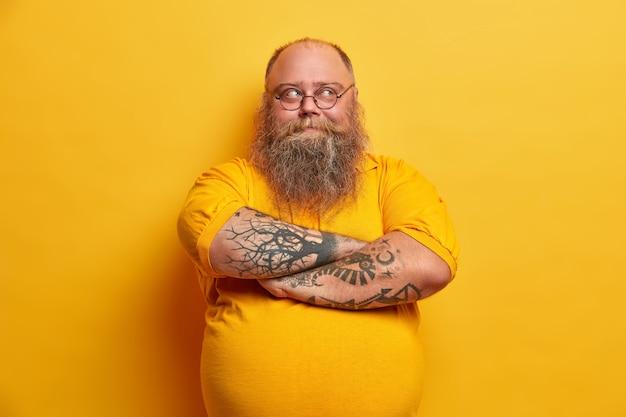 Przystojny, brodaty mężczyzna trzyma założone ręce, rozgląda się w zamyśleniu, ma pulchne ciało, ubrany w zwykły strój, wymyśla plan odchudzania, odizolowany na żółtej ścianie. zamyślony niezdecydowany facet