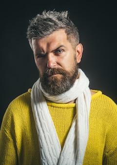Przystojny brodaty mężczyzna ubrany w jesienną lub zimową odzież casual wygląda atrakcyjny mężczyzna ze stylowym