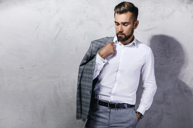 Przystojny brodaty mężczyzna ubrany w szary garnitur pozuje przed betonową ścianą