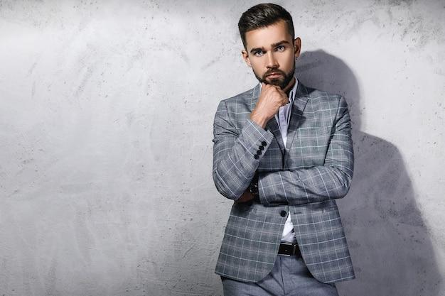 Przystojny brodaty mężczyzna ubrany w szary garnitur w kratkę pozuje przed betonową ścianą