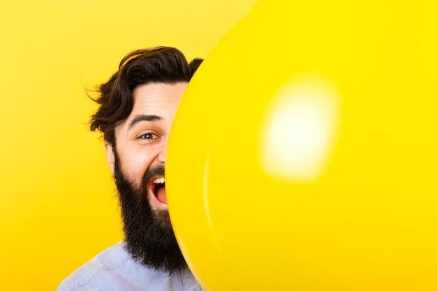 Przystojny brodaty mężczyzna uśmiecha się z góry żółty balon na żółtym tle, pozytywne emocje