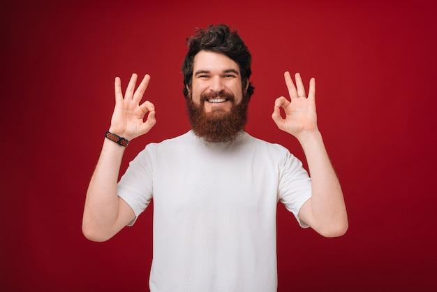 Przystojny brodaty mężczyzna w białej koszulce na czerwonej ścianie pokazujący znak ok