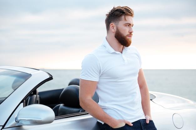 Przystojny brodaty mężczyzna w białej koszuli, opierając się na samochodzie, stojąc na plaży