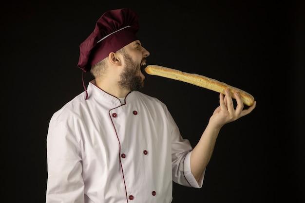 Przystojny brodaty mężczyzna w mundurze gryzie bagietki, mężczyzna piekarz kucharz