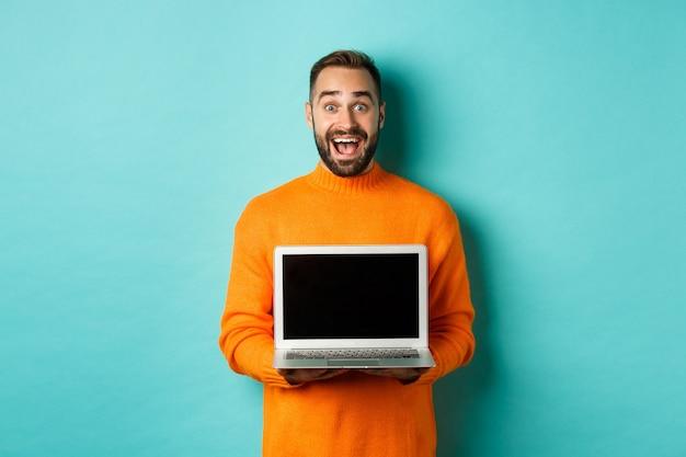 Przystojny brodaty mężczyzna w pomarańczowym swetrze pokazuje ekran laptopa, demonstrując promocję