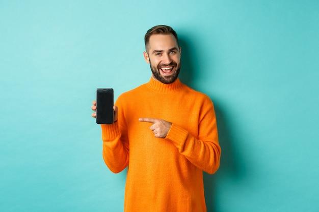 Przystojny brodaty mężczyzna w pomarańczowym swetrze, wskazując palcem na ekran telefonu komórkowego, pokazując aplikację smartphone, stojąc na jasnoniebieskim tle.