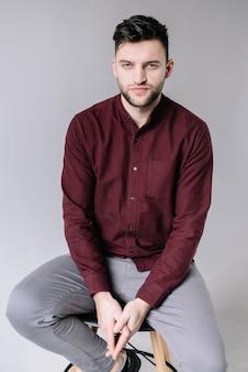 Przystojny brodaty mężczyzna w przypadkowych ubraniach na szarości ścianie