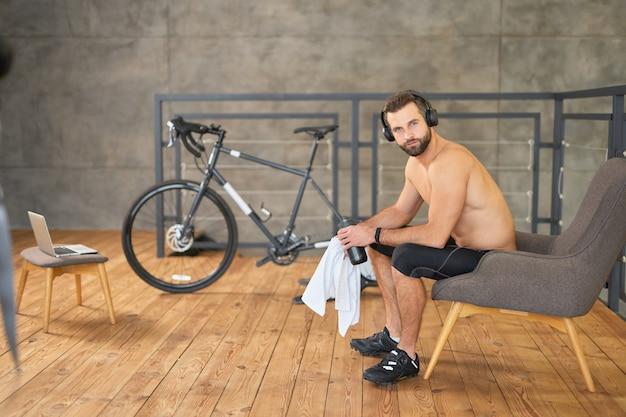 Przystojny brodaty mężczyzna w słuchawkach trzymający butelkę wody i uśmiechający się podczas odpoczynku w pokoju z rowerem treningowym