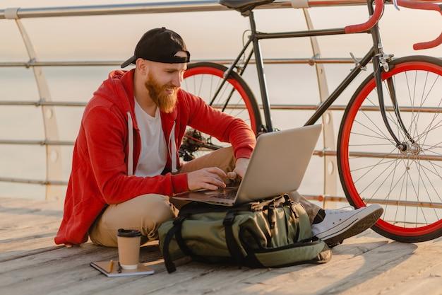 Przystojny Brodaty Mężczyzna W Stylu Hipster Pracujący Online Freelancer Na Laptopie Z Plecakiem I Rowerem W Porannym Wschodzie Słońca Nad Morzem Zdrowy Aktywny Styl życia Podróżnik Z Plecakiem Darmowe Zdjęcia