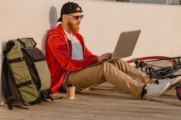 Przystojny brodaty mężczyzna w stylu hipster pracujący online freelancer na laptopie z plecakiem i rowerem w porannym wschodzie słońca nad morzem zdrowy aktywny styl życia podróżnik z plecakiem