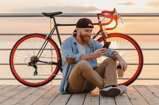 Przystojny brodaty mężczyzna w stylu hipster w dżinsowej koszuli i czapce, trzymając smartfon z rowerem w poranny wschód słońca nad morzem, pije kawę, podróżnik zdrowego, aktywnego stylu życia
