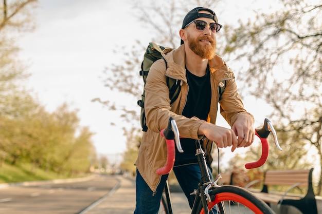 Przystojny brodaty mężczyzna w stylu hipster w kurtce i okularach przeciwsłonecznych, jeżdżący sam z plecakiem na rowerze, podróżnik zdrowego, aktywnego stylu życia