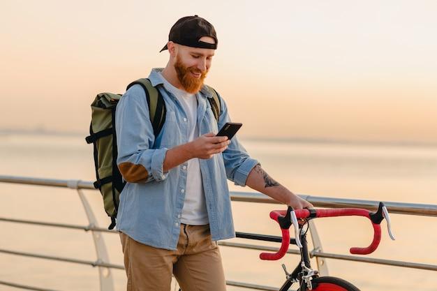 Przystojny brodaty mężczyzna w stylu hipster z plecakiem w dżinsowej koszuli i czapce z rowerem o porannym wschodzie słońca nad morzem pije kawę, zdrowy, aktywny styl życia podróżnik z plecakiem