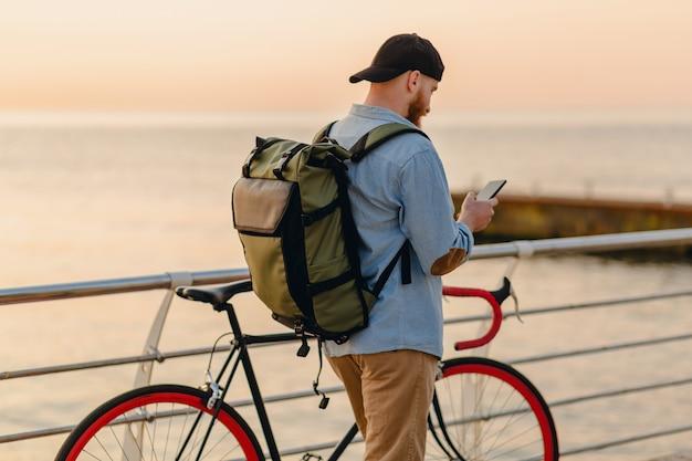 Przystojny brodaty mężczyzna w stylu hipster za pomocą telefonu podróżującego z plecakiem i rowerem w poranny wschód słońca nad morzem, podróżnik zdrowego, aktywnego stylu życia