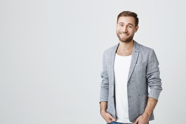 Przystojny brodaty mężczyzna w szarej kurtce uśmiechnięta kamera