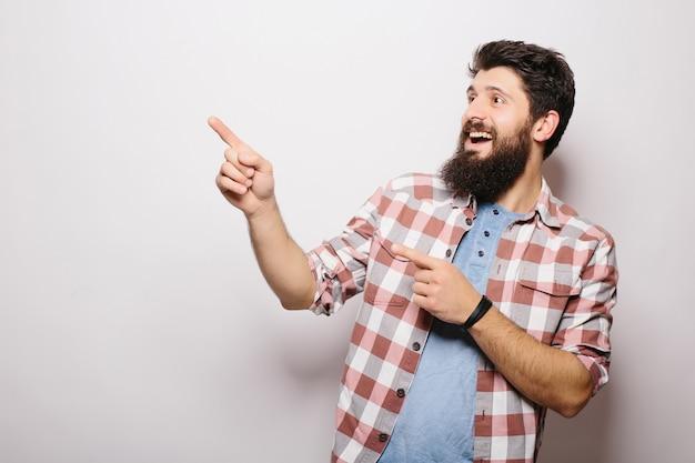 Przystojny brodaty mężczyzna w ubranie wskazuje, uśmiechnięty, na szarej ścianie
