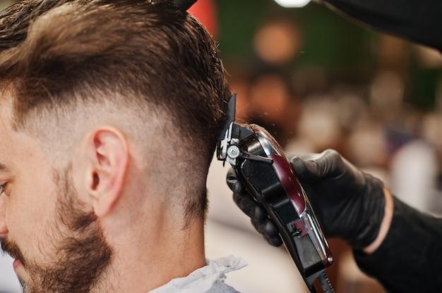 Przystojny brodaty mężczyzna w zakładzie fryzjerskim, fryzjer w pracy. bliska kark.