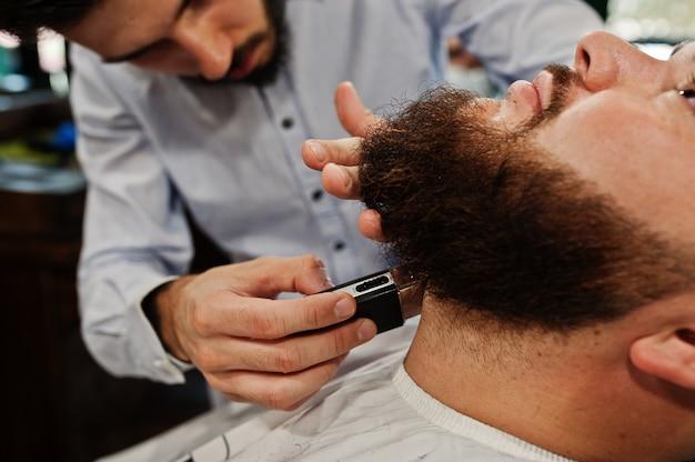 Przystojny brodaty mężczyzna w zakładzie fryzjerskim, fryzjer w pracy.