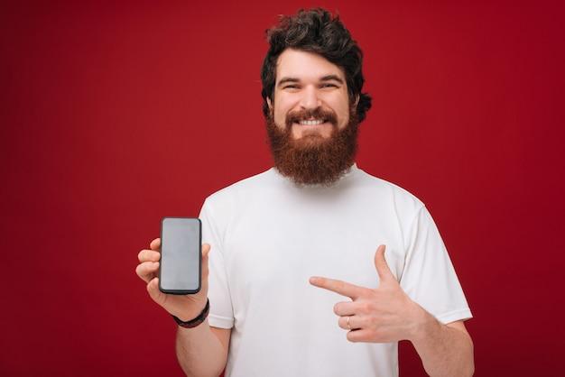 Przystojny brodaty mężczyzna wskazując na telefon komórkowy z uśmiechem toothy