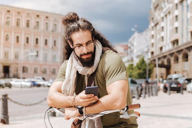 Przystojny brodaty mężczyzna za pomocą swojego smartfona, stojąc na środku ulicy