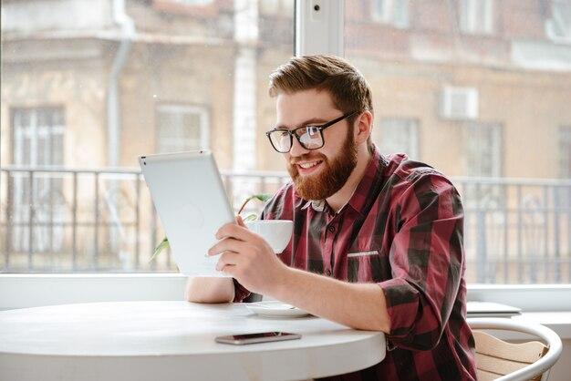 Przystojny brodaty młody człowiek używa pastylka komputer.