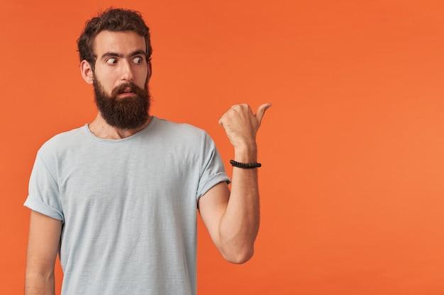 Przystojny brodaty młody mężczyzna o brązowych oczach, ubrany w białą koszulkę, pokazuje palec w prawo emocje zaskoczony lub zdezorientowany, patrząc na bok